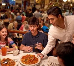 Food server placing large plate of food on table