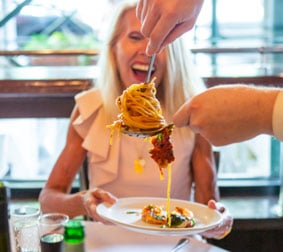 Food server twirling pasta on a spoon
